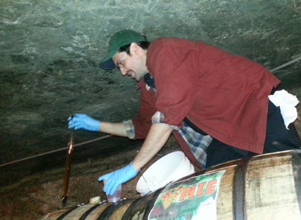 Jason Heystek pulls a barrel sample at Founders Brewing