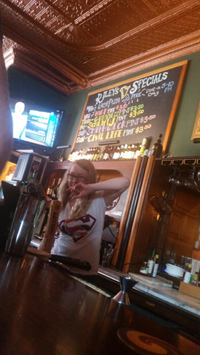 A bartender at Riley's Pub tends to the taps