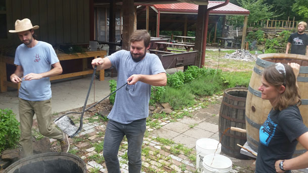Jeff Stuffings delivers hot stones to boiling barrel at Scratch Brewing